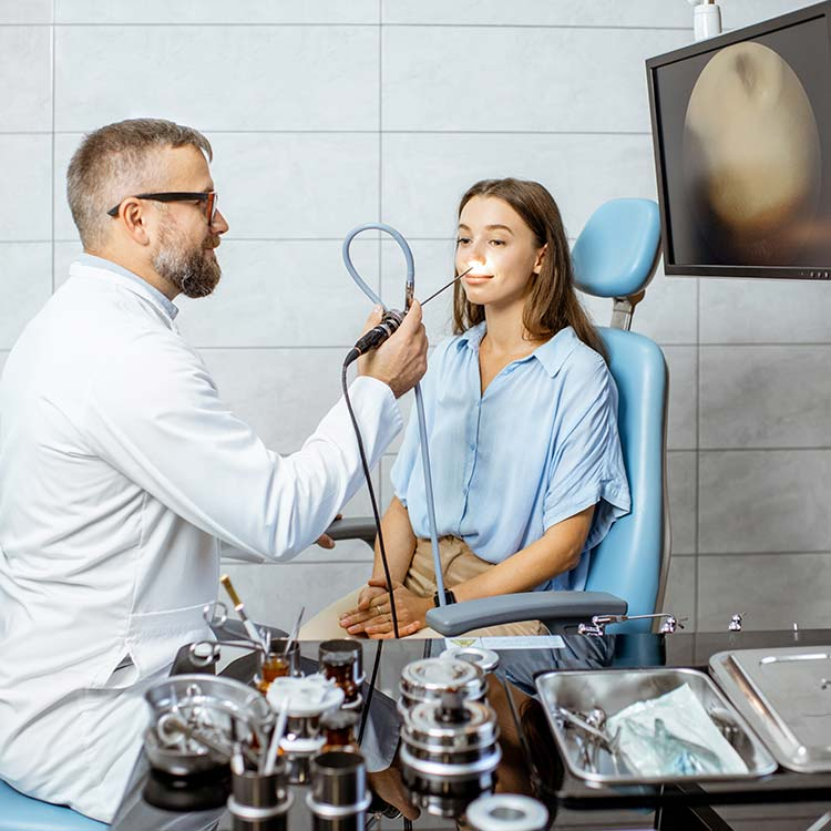 Ear, nose, and throat doctor examining a patient with a scope